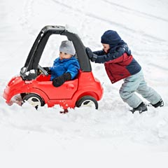 a boy pushing a girl in a toy car in the snow